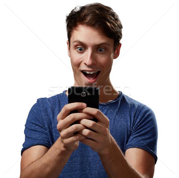 Meglepett férfi okostelefon fiatalember fehér boldog Stock fotó © Kurhan