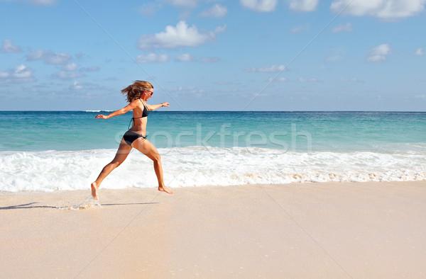 Happy woman running on the beach. Stock photo © Kurhan