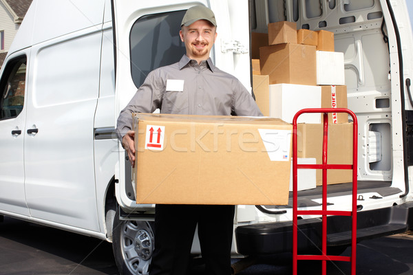 Young delivery man with parcel. Stock photo © Kurhan