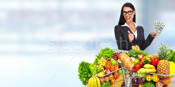 Happy young woman with grocery shopping cart and American dollars. Stock photo © Kurhan