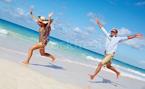 Happy couple running on the beach. Stock photo © Kurhan