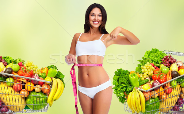 Woman with measuring tape over green background. Stock photo © Kurhan