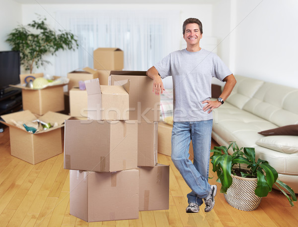 Man with moving boxes in new apartment. Stock photo © Kurhan