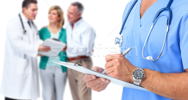 Doctor hands writing on a clipboard. Stock photo © Kurhan