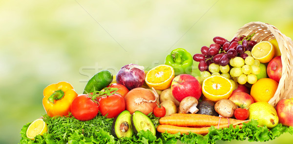 Fruits and vegetables over green background. Stock photo © Kurhan