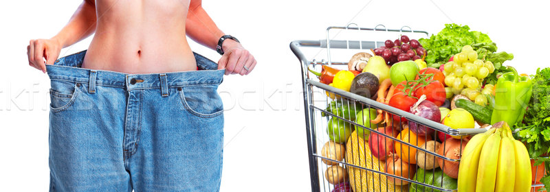 Slimming woman wearing big pants over white background. Stock photo © Kurhan