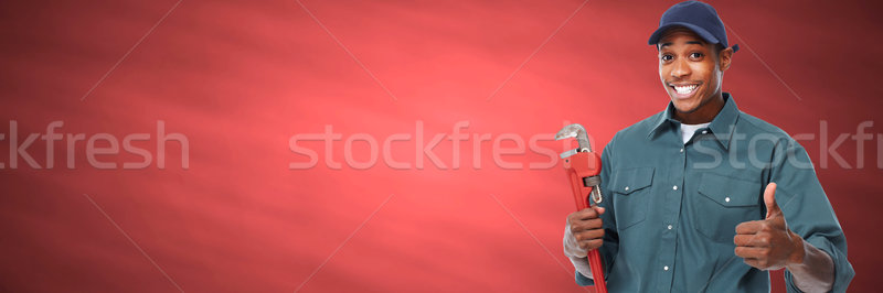 African american handyman plumber with a wrench. Stock photo © Kurhan