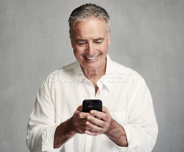 Mosolyog idős férfi okostelefon szöveges üzenet telefon Stock fotó © Kurhan