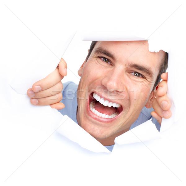 Сток-фото: молодым · человеком · Cute · улыбаясь · глядя · дыра · бумаги