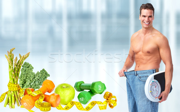 Slimming man wearing big jeans. Stock photo © Kurhan