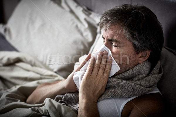 Sick man with cold lying in bed and blow nose. Stock photo © Kurhan