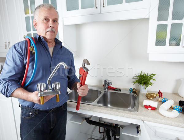 Hands of Plumber with a wrench. Stock photo © Kurhan