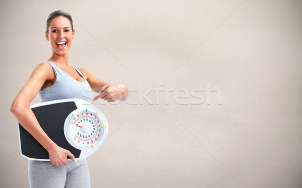 Woman with scales over gray background. Stock photo © Kurhan