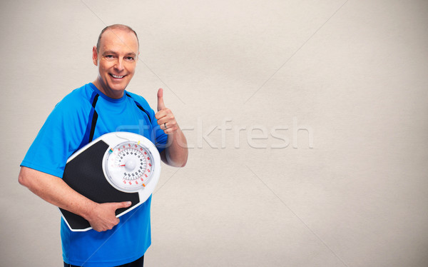 Man with scales over gray background. Stock photo © Kurhan