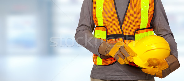 Worker with helmet in orange security vest. Stock photo © Kurhan