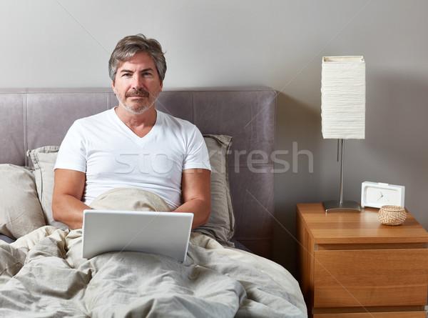 Férfi laptop ágy jóképű férfi megnyugtató otthon Stock fotó © Kurhan