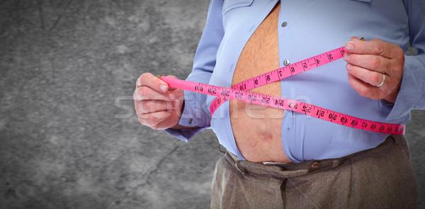 Obese man abdomen with measuring tape. Stock photo © Kurhan