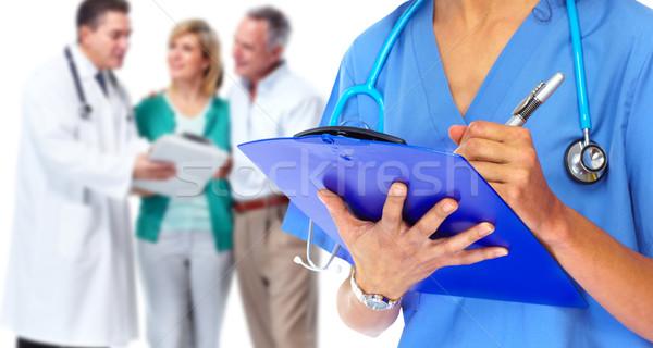 Doctor hands writing on a clipboard. Stock photo © Kurhan