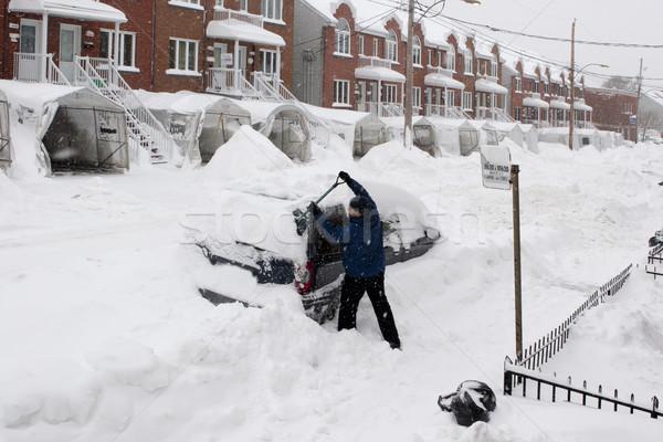 Man with a snow shovel. Snowfall in the city. Stock photo © Kurhan
