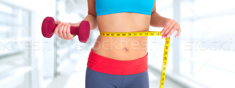 Woman abdomen with measuring tape over blue background. Stock photo © Kurhan