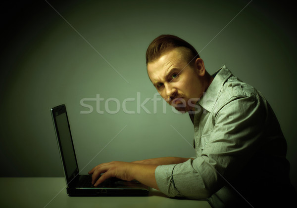 Young dissatisfied man working with laptop. Stock photo © Kurhan