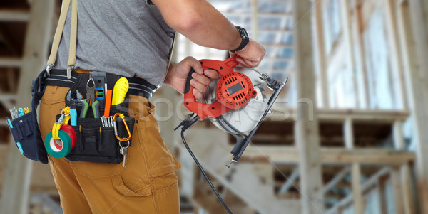 Hands of construction builder with electric saw. Stock photo © Kurhan