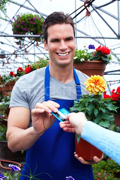 Florist man working with flowers in greenhouse. Stock photo © Kurhan