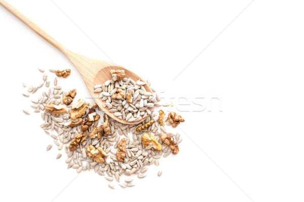 Dried peeled sunflower seeds with walnuts on wooden spoon isolat Stock photo © kurkalukas