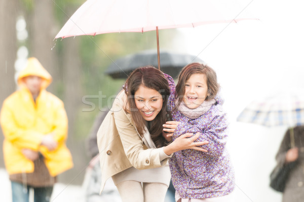 Mother and child under umbrella in rainy weather. Stock photo © kyolshin