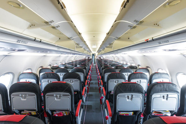 Vanishing row of black and red seats in airplane. Stock photo © kyolshin