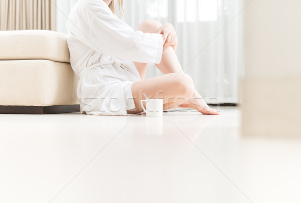 Mulher branco roupão de banho sessão piso quarto de hotel Foto stock © kyolshin