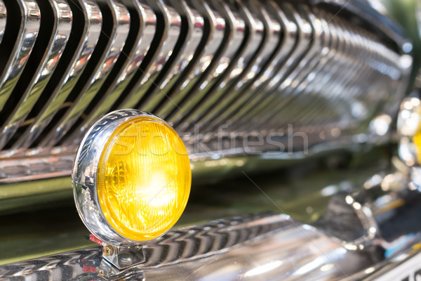 Yellow head light of retro car and radiator grille. Stock photo © kyolshin