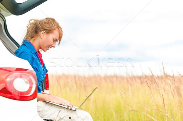 Woman in meadow near car working on laptop. Stock photo © kyolshin