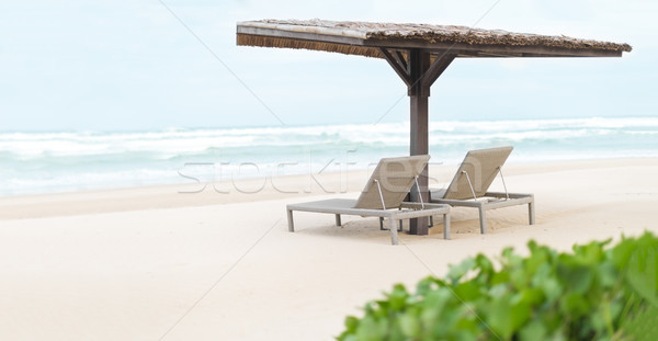 Two empty chaise longues under shed on beach. Stock photo © kyolshin