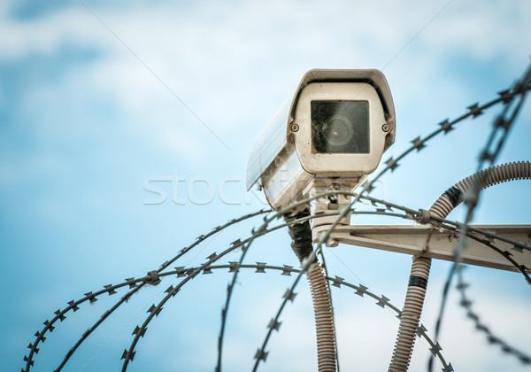 Observation camera and barbwire on blue sky. Stock photo © kyolshin