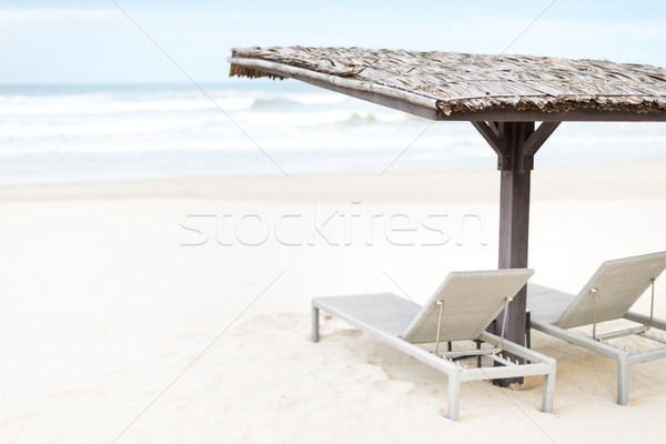 Stock photo: Two empty chaise longues under shed on beach.