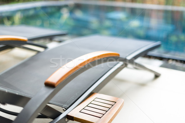 Empty chaise longues near swimming pool. Stock photo © kyolshin