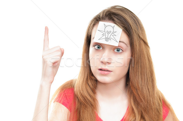 Girl with light bulb on paper on her forehead. Stock photo © kyolshin