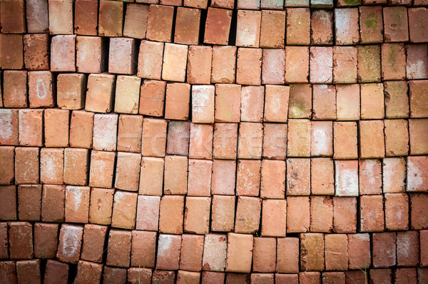 Wall of new red bricks stacked in rows. Stock photo © kyolshin