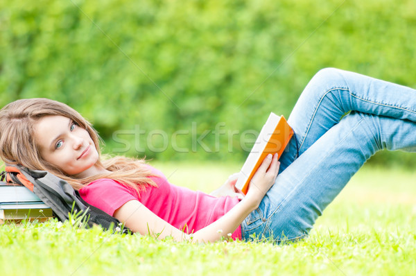 happy student girl lying on grass with opened book Stock photo © kyolshin