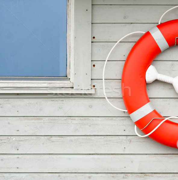 Orange lifebuoy on white wall in port Stock photo © kyolshin