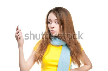 Surprised girl holding phone in her hand. Stock photo © kyolshin
