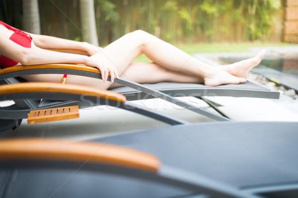 Elegant girl in swimsuit lying on sun lounger. Stock photo © kyolshin