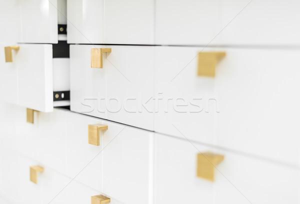 White sleek drawers with golden handles. Stock photo © kyolshin