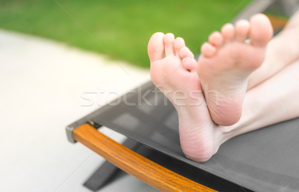 Feet and soles of person lying on sunbed. Stock photo © kyolshin