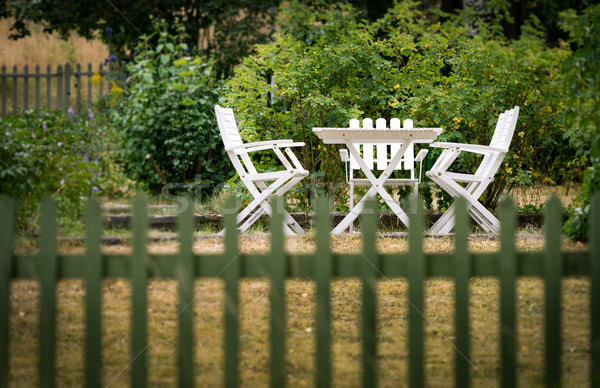 Garden chairs and table behind fence Stock photo © kyolshin