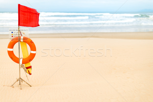 Life saving objects with red flag on beach. Stock photo © kyolshin