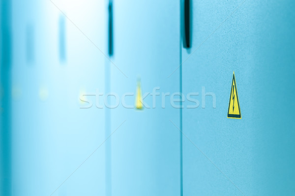 Yellow high voltage sign on blue doors. Stock photo © kyolshin