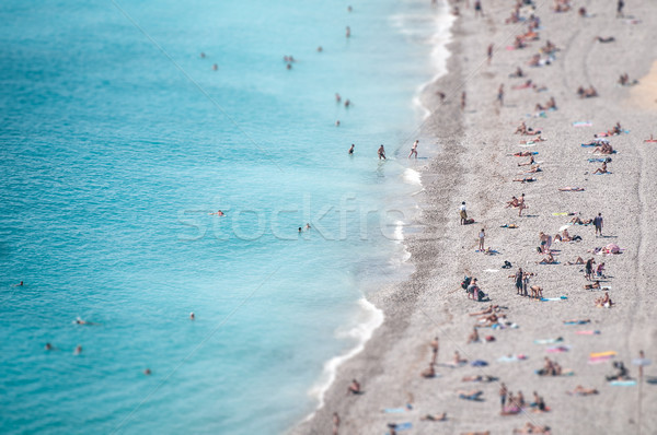 Ocean beach with people bathing and tanning. Stock photo © kyolshin
