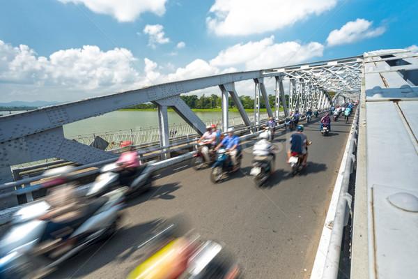 People on bikes on bridge of Hue, Vietnam, Asia. Stock photo © kyolshin